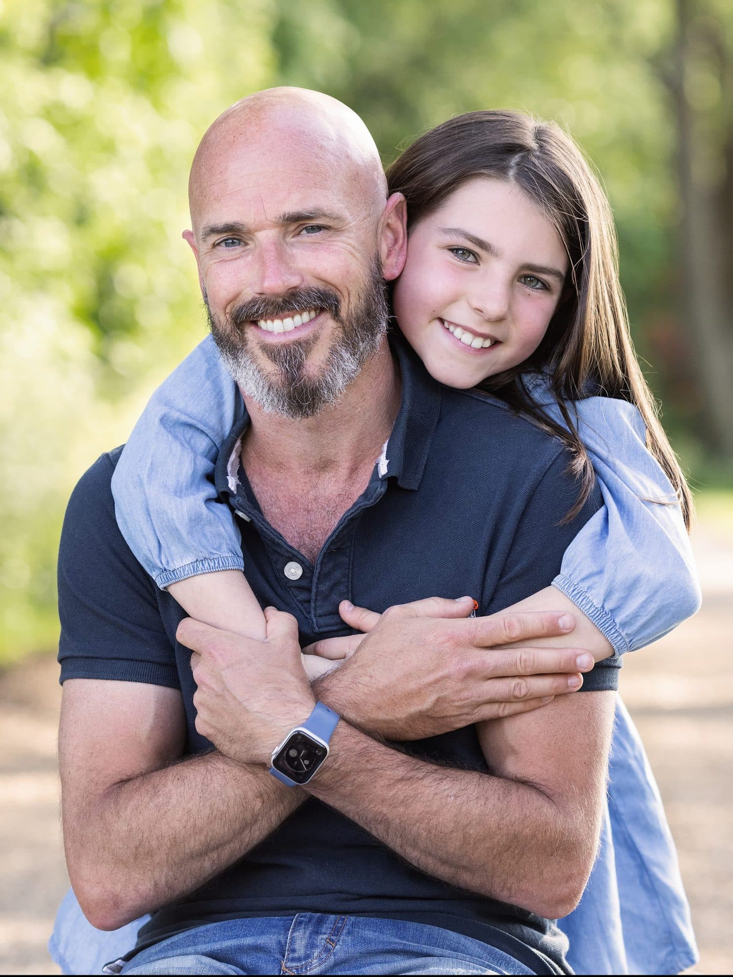 Little Girl smiles and hugs her Dad during Summer Outdoor Family Photoshoot on Suffolk farm