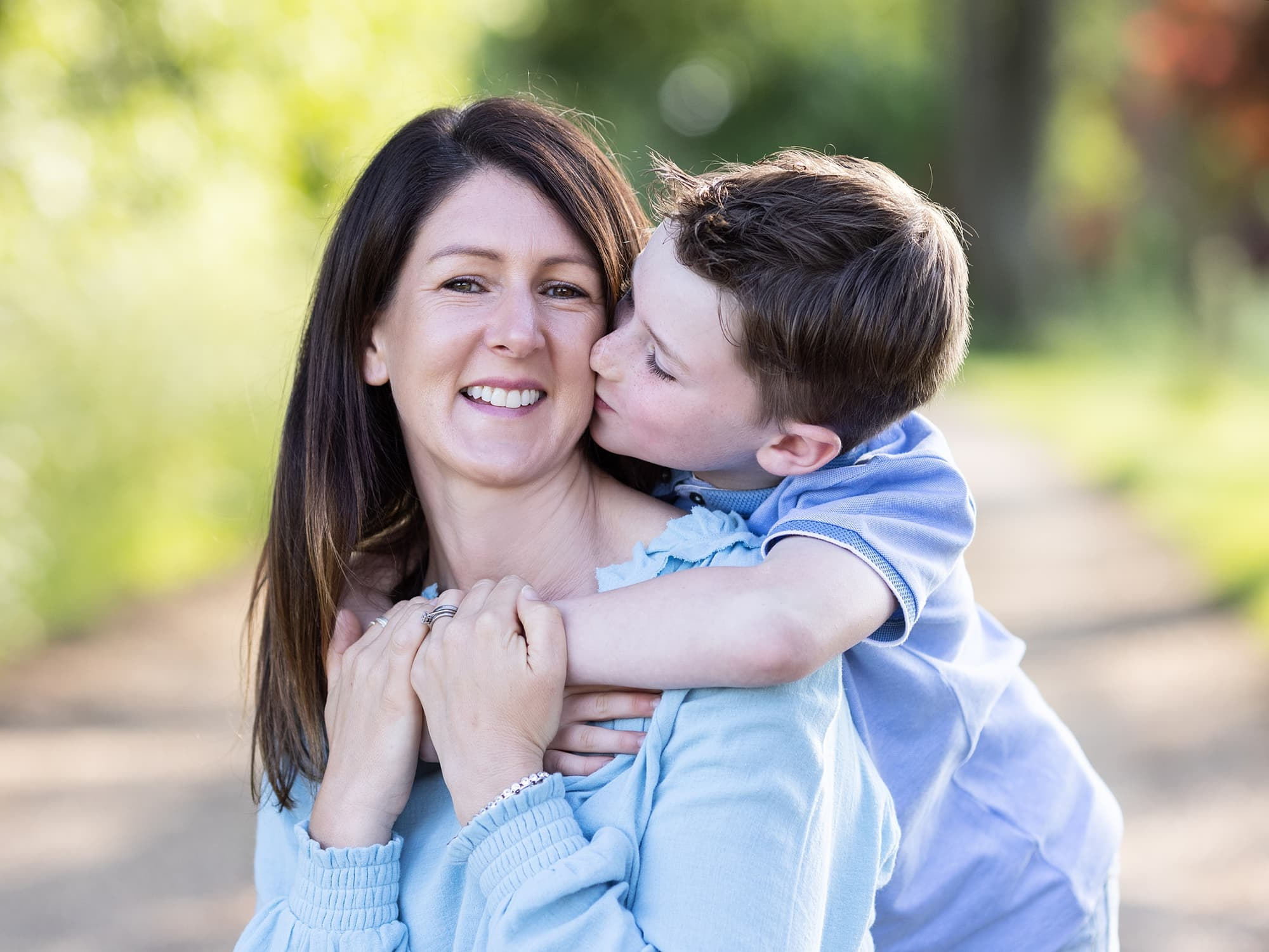 Little boy kisses his Mothers cheek during outdoor family photoshoot in Suffolk Countryside