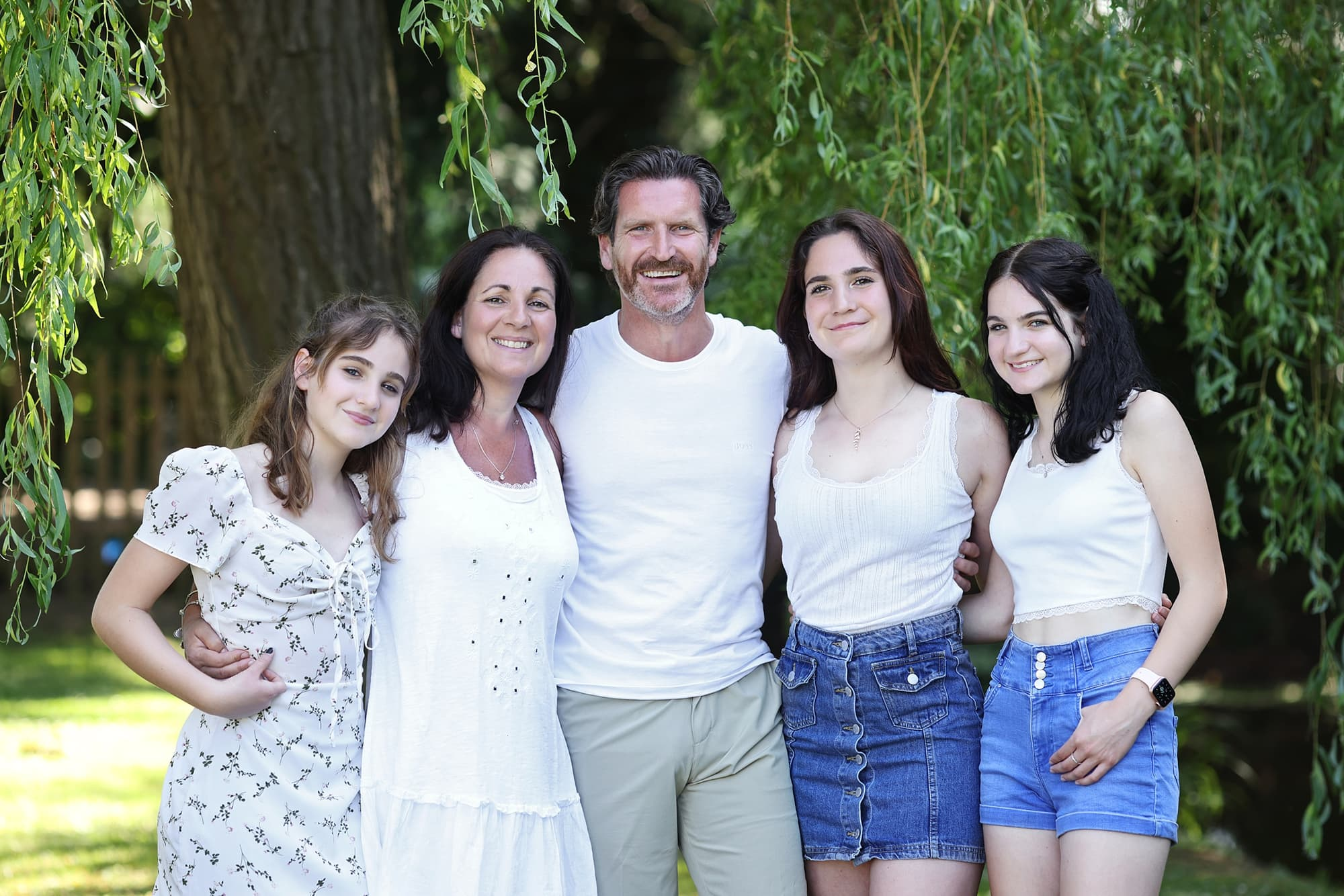 Family of 5 stand and pose for photo next to a green tree with white blossom