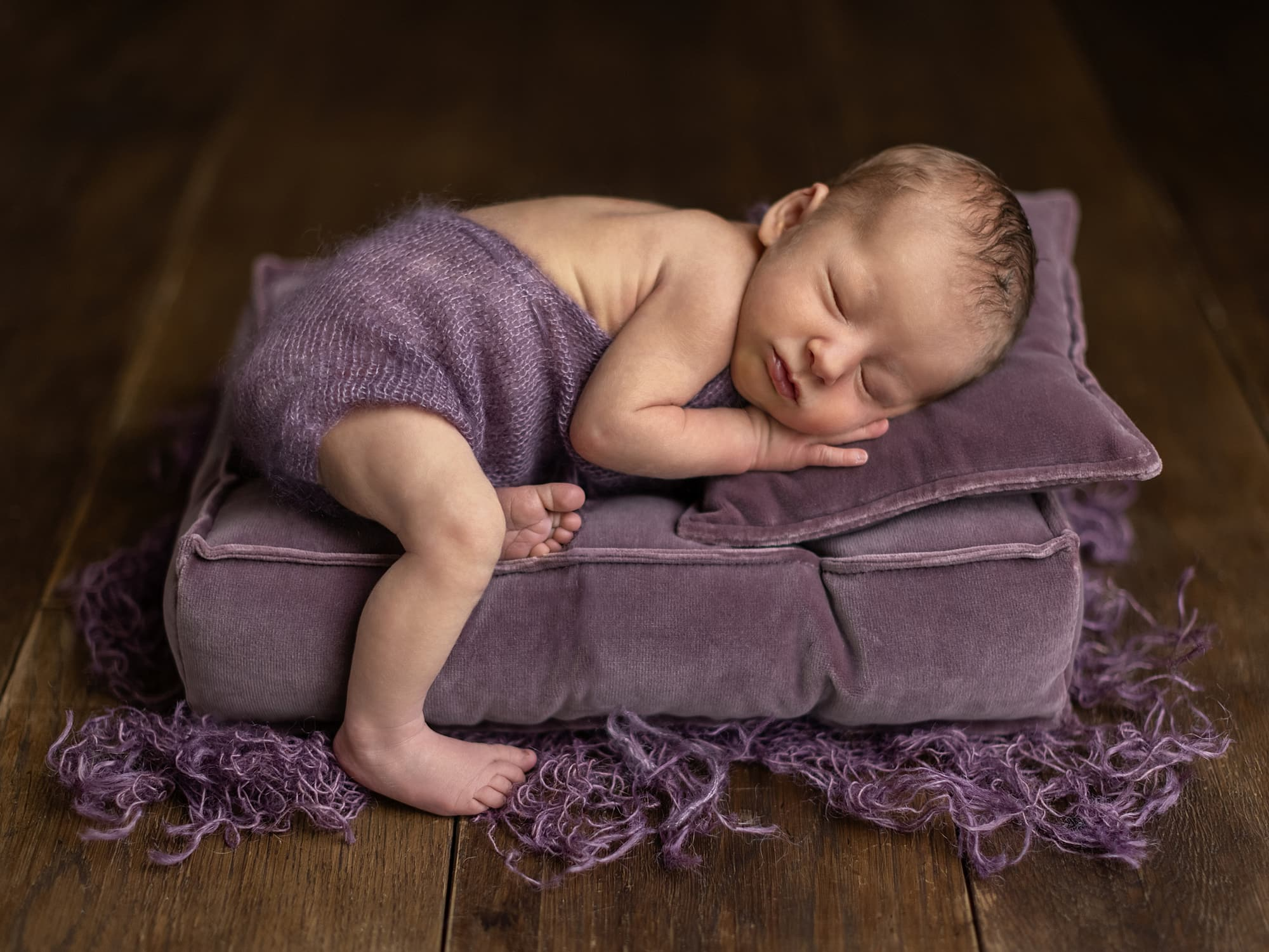 Baby girl in purple romper lies on her tummy on a purple mattress and pillow during Newborn Shoot at Suffolk Studio