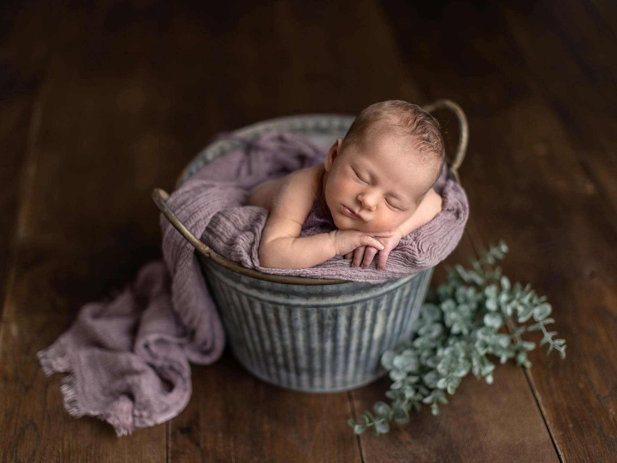 Baby girl in tin bucket and purple scarf lies with her head on her hands during Newborn Shoot at Suffolk Studio