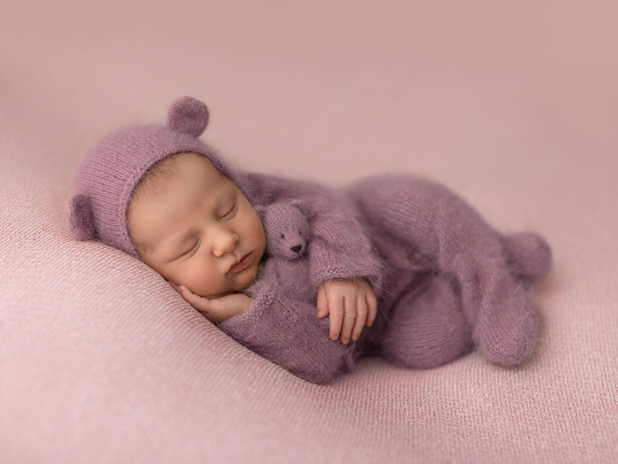 Baby girl in purple romper and teddy hat lies on her side on a pink background during Newborn Shoot at Suffolk Studio