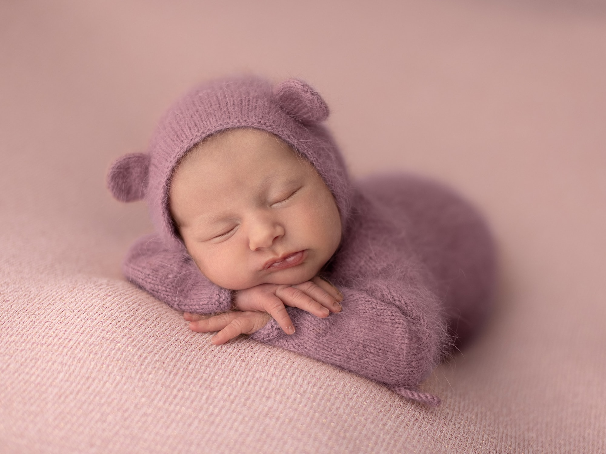 Baby girl in purple romper and teddy hat rests her head on her hands on a pink background during Newborn Shoot at Suffolk Studio