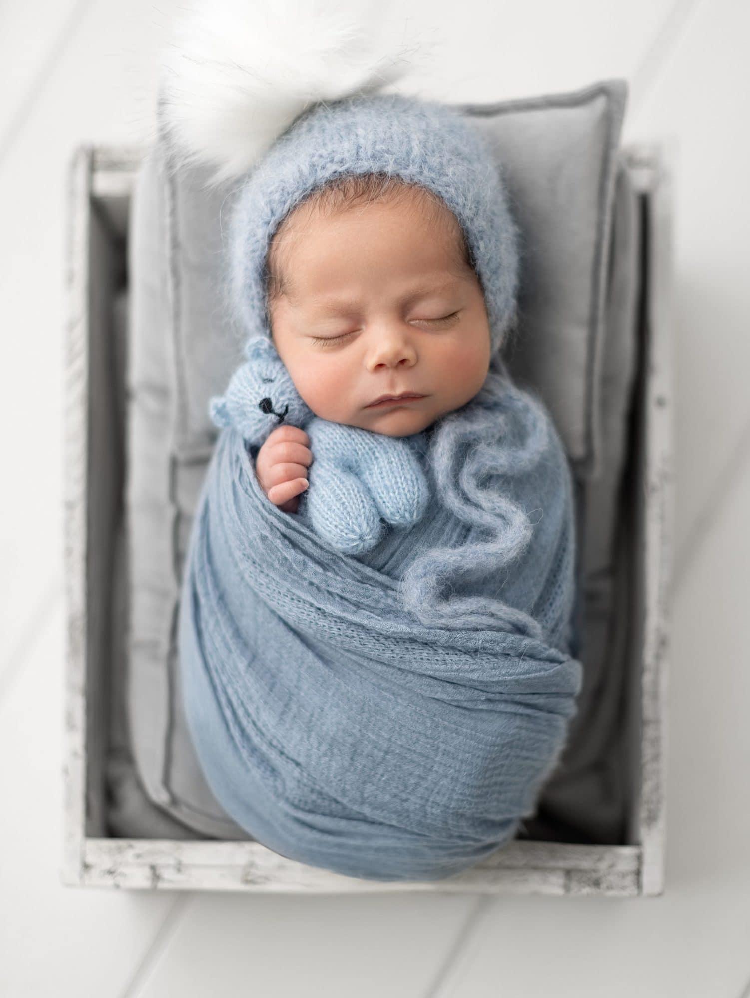 Baby boy in white wooden crate cuddles his blue teddy during his Newborn Photoshoot in Suffolk Studio