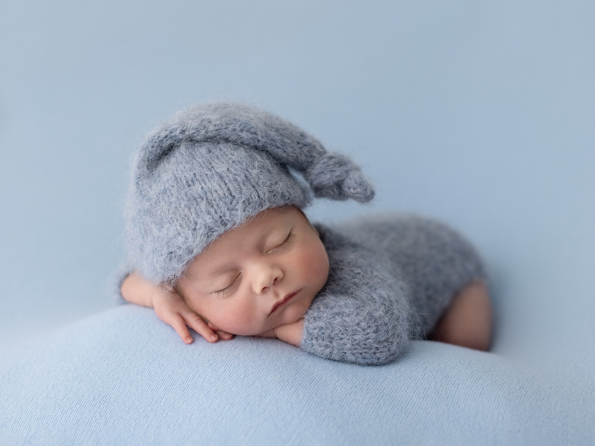 Baby boy in blue wool romper and sleepy hat lying on his front during his Newborn Photoshoot in Suffolk Studio