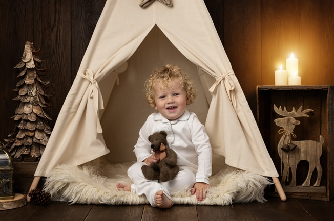 Smiling Toddler sat in Christmas Mini Photoshoot Teepee holding a brown teddy