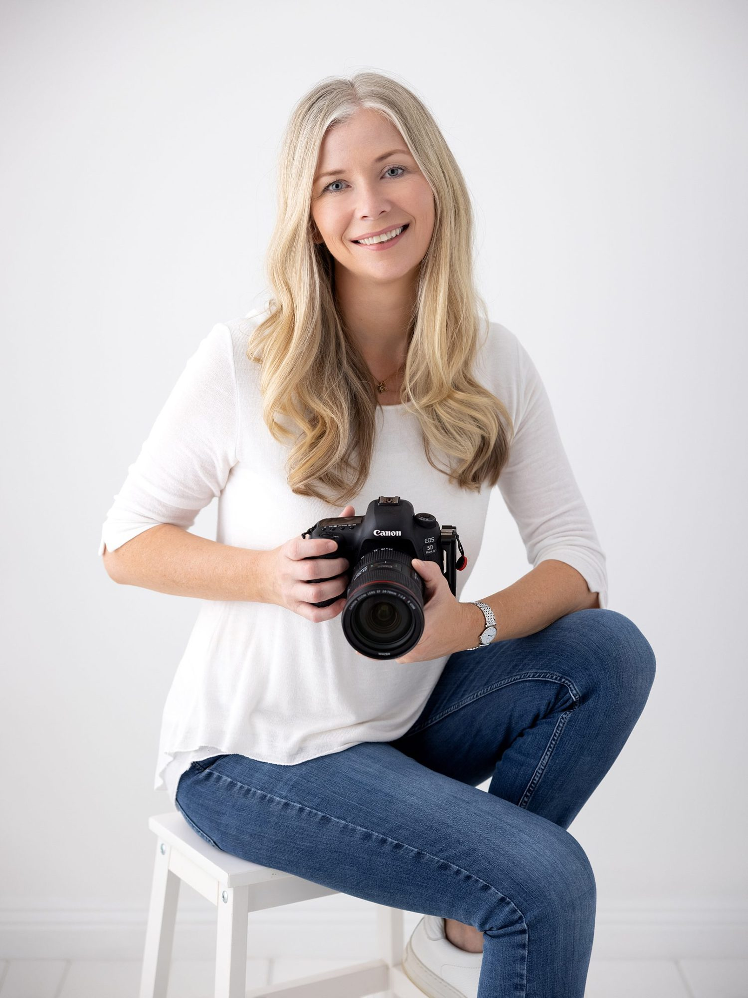 Alison McKenny the Photographer in a white top and jeans against a white studio backdrop