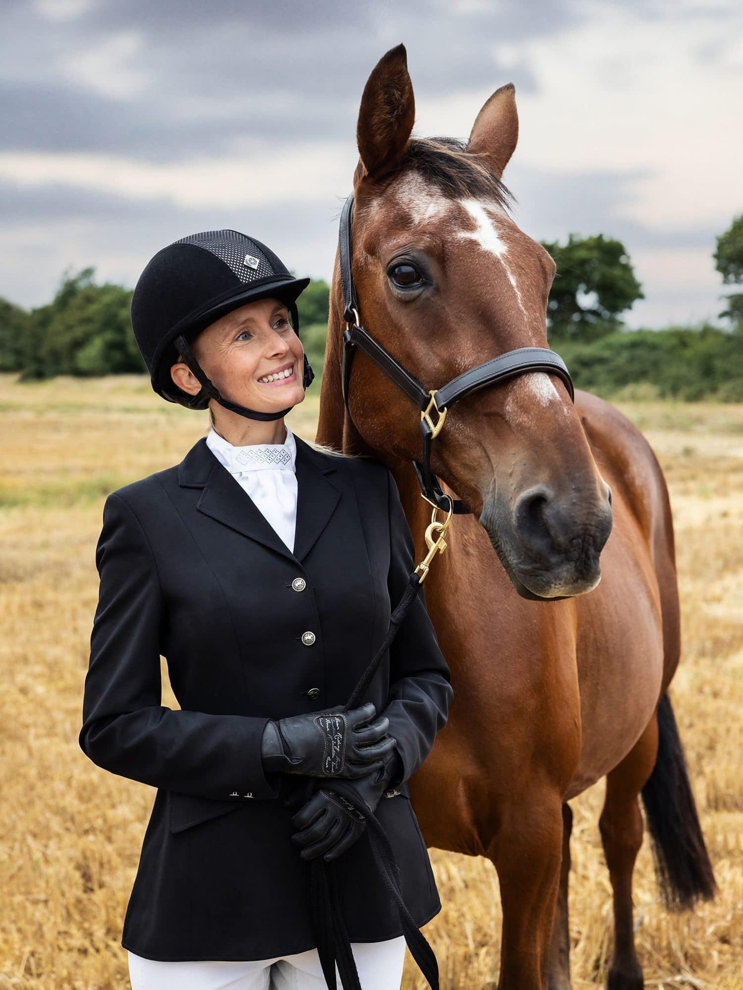 Horse and rider pose for a photograph in a stubble field in Suffolk countryside