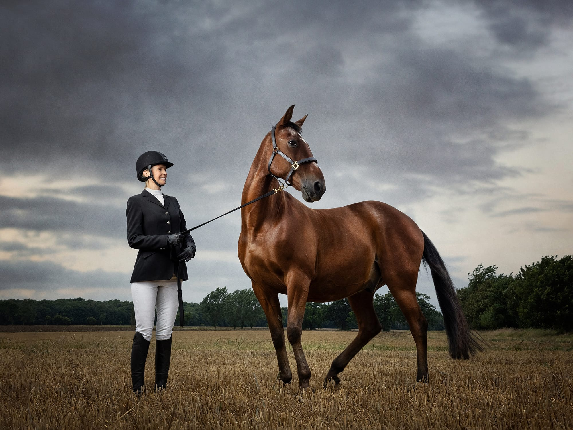 Fine Art Portrait of a horse and rider in a Suffolk field with a dramatic cloudy sky