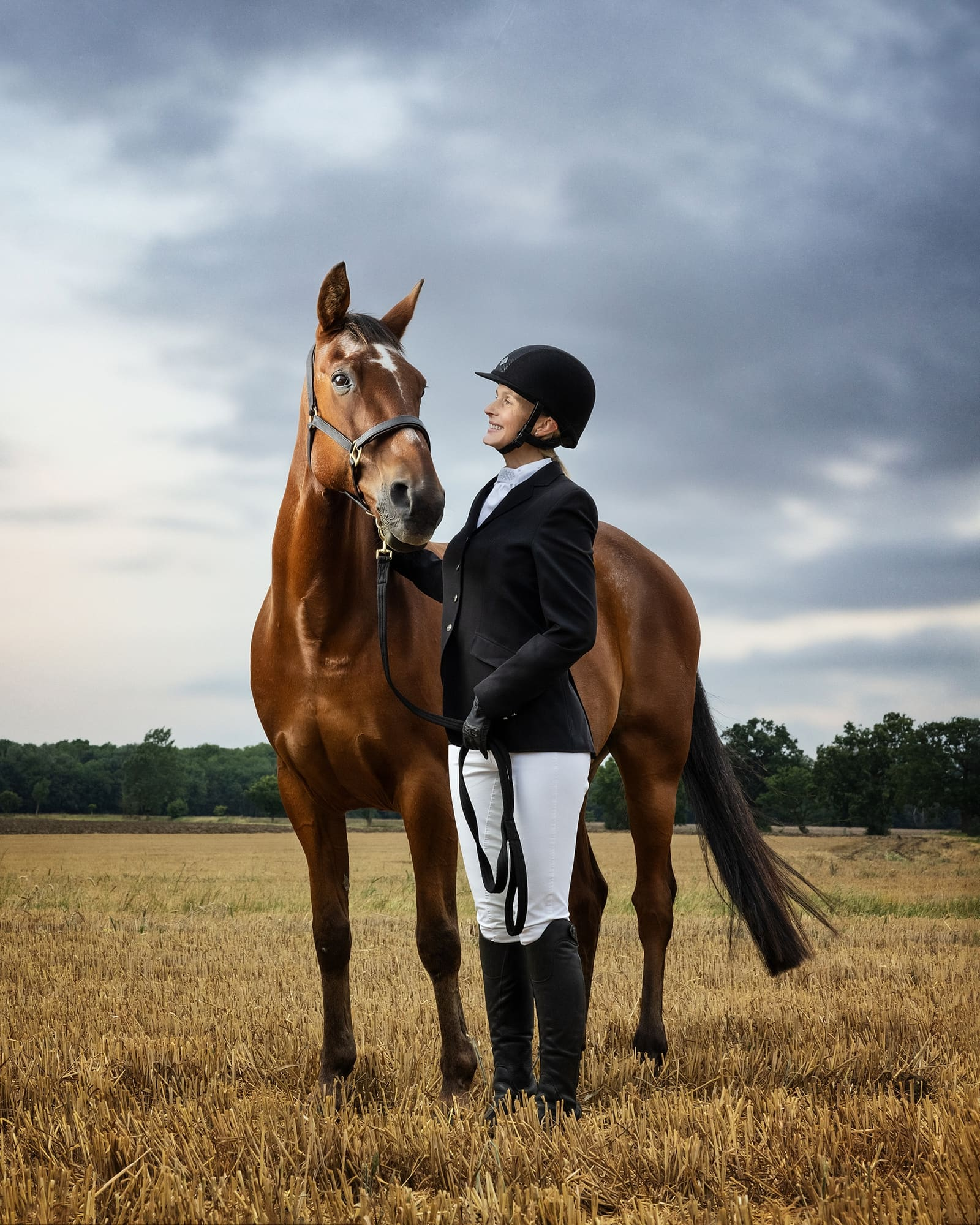 Portrait of a horse and jockey in a Suffolk field with a dramatic cloudy sky