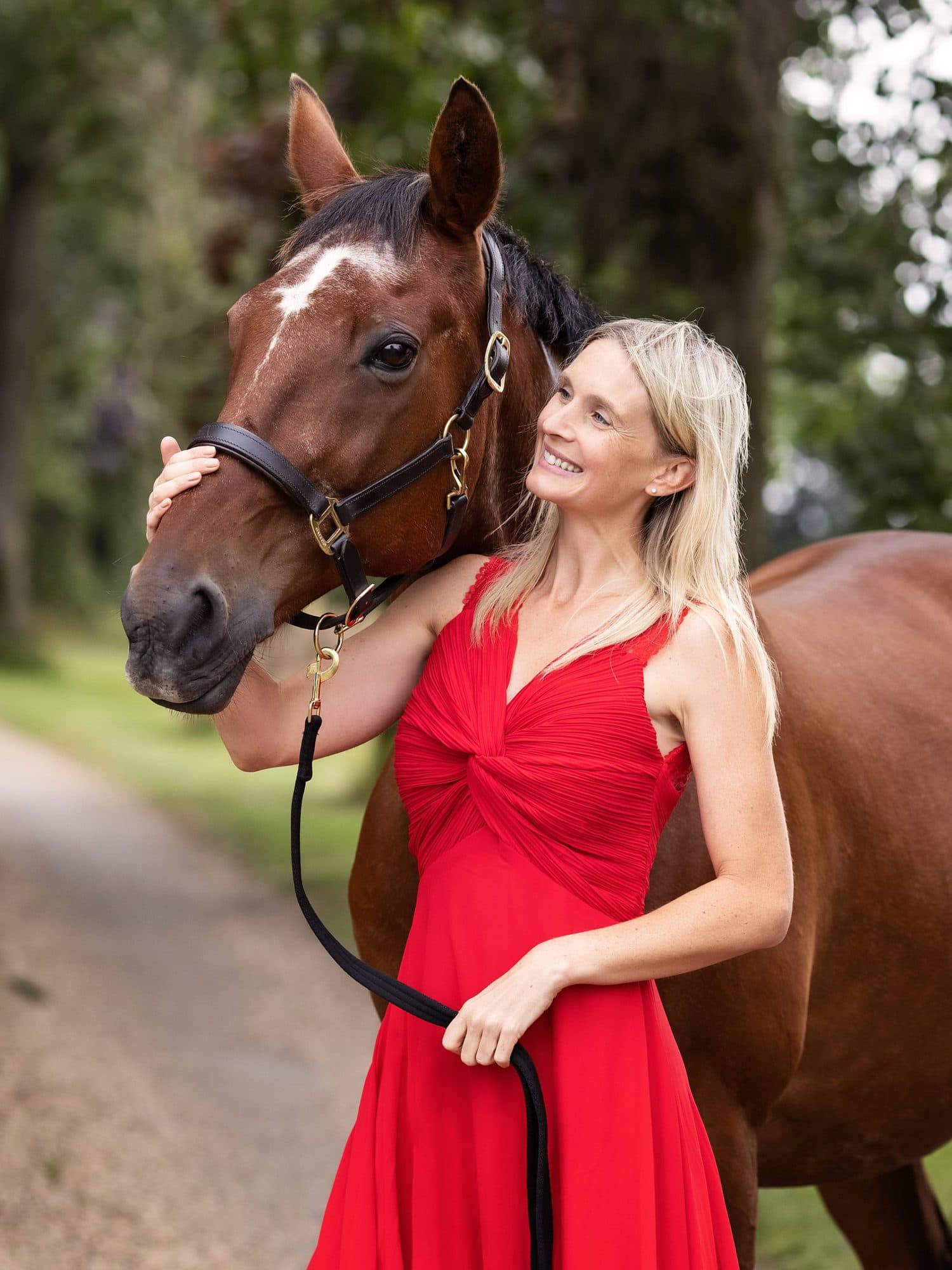 Photo of a Lady in red dress smiles at her beautiful bay horse on a country lane