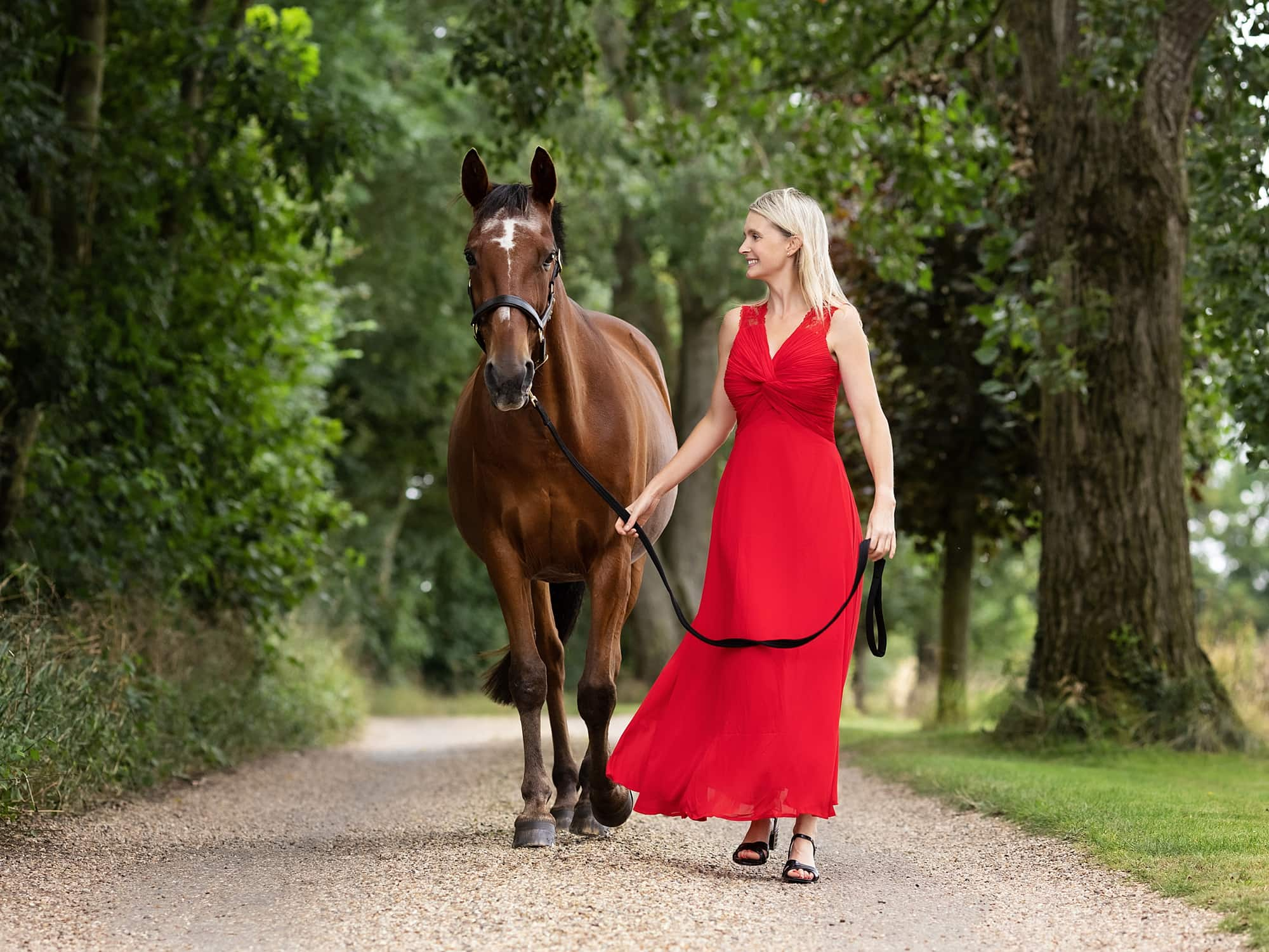 Photograph of a lady in red dress walking her horse on a country lane