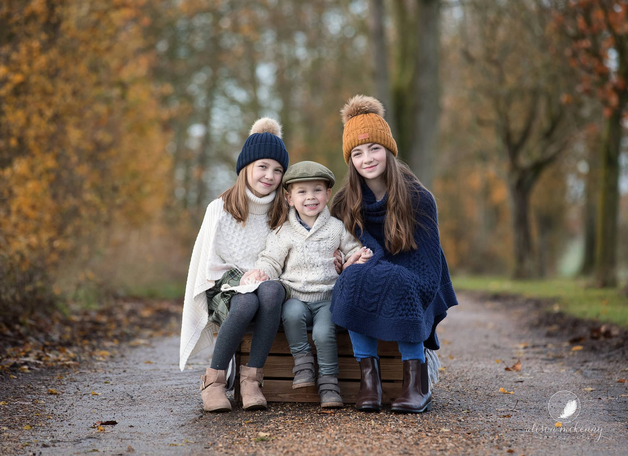 Autumnal photo of 3 siblings in warm jumpers and hats on Suffolk farm