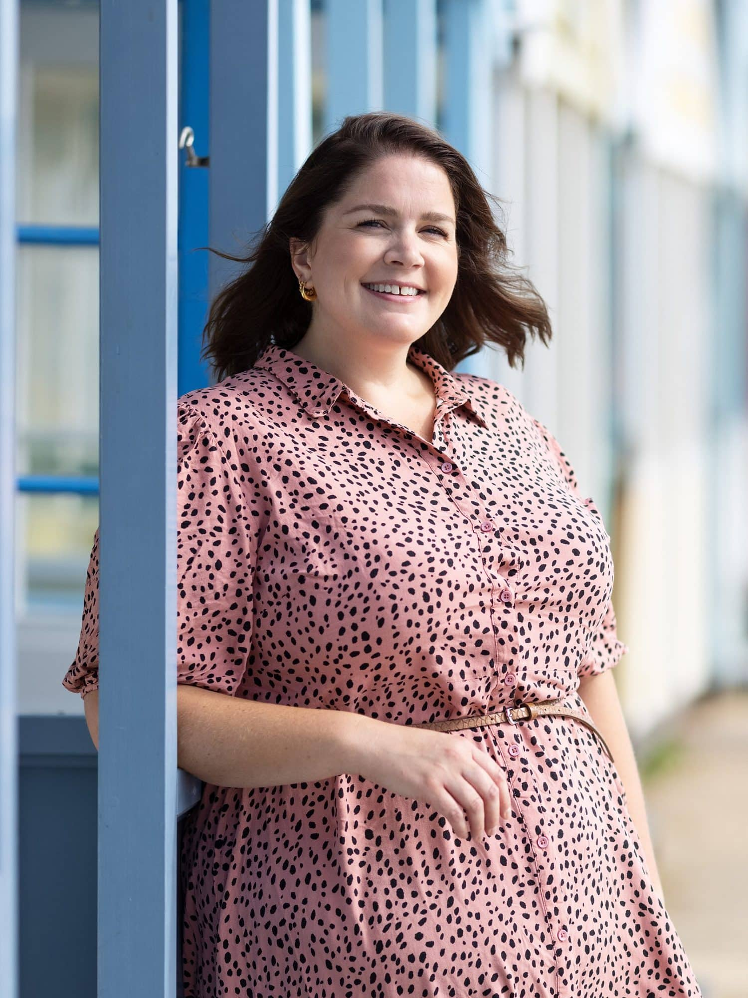Lady in pink dress poses for a Personal Branding Headshot by Beach huts in Southwold